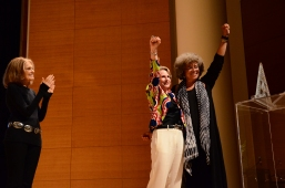 After receiving her award, Angela Davis and Elizabeth Sackler raise their fist to the crowd.